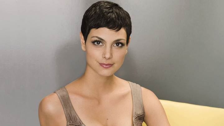 Morena Baccarin Sitting On Yellow Sofa In Brown Top