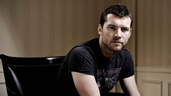 Sam Worthington In Black T-Shirt Sitting On Chair
