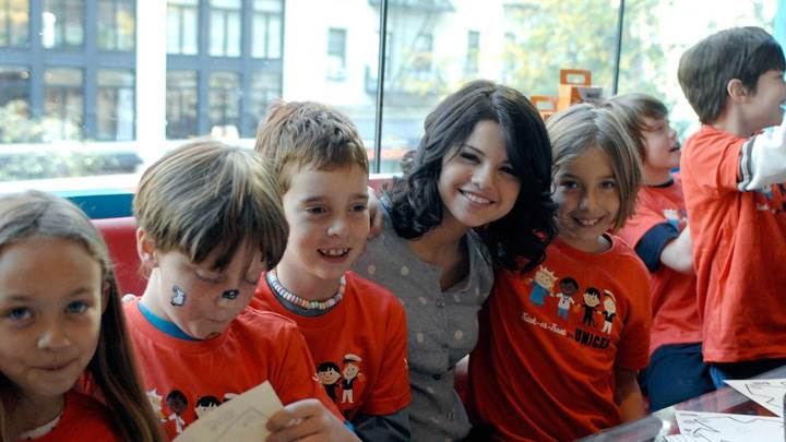 Selena Gomez Sitting With Kids Smiling