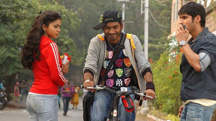 Shriya Saran In Red Top Side Pose N Dhanush On Bicycle In Kutty Movie