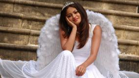 Sneha Ullal Smiling Sitting Pose In White Dress N Crown On Head