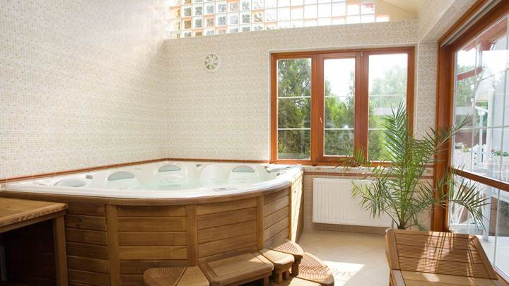 Wooden Bathtub And White Interior In Bathroom