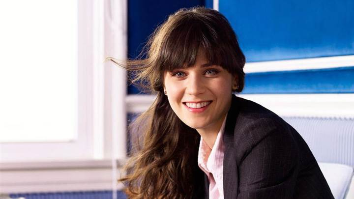 Smiling Zooey Deschanel In Black Coat Looking At Camera