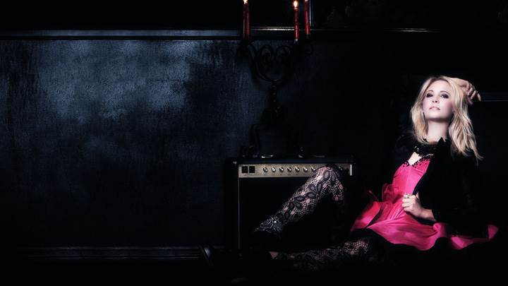 Candice Accola Sitting On A Black Sofa With Guitar