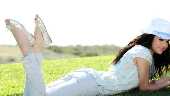Selena Gomez Smiling Laying Pose on Grass In Garden
