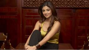 Smiling Pose Of Shilpa Shetty Sitting on A Wooden Bench