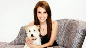 Emma Roberts Sitting And Smiling With White Dog