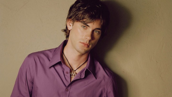 Drew Fuller In Purple Shirt Standing Along The Wall