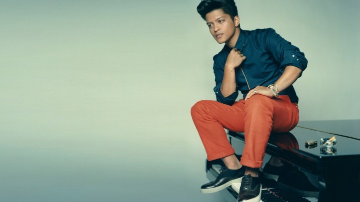 Bruno Mars Sitting On Piano In Red Pant And Blue Shirt