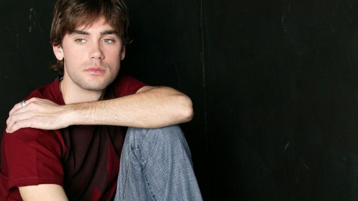 Drew Fuller Sitting In Red T-Shirt And Blue Denim