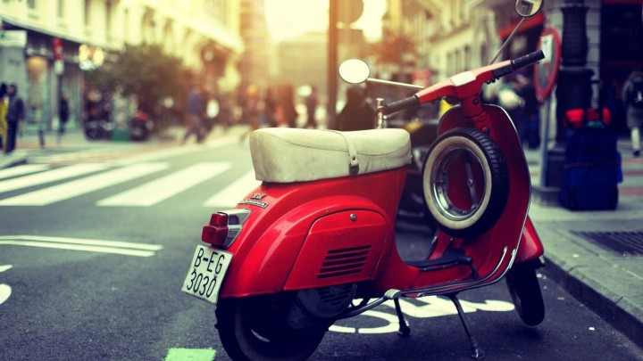 Red Vespa Standing On The Road Side